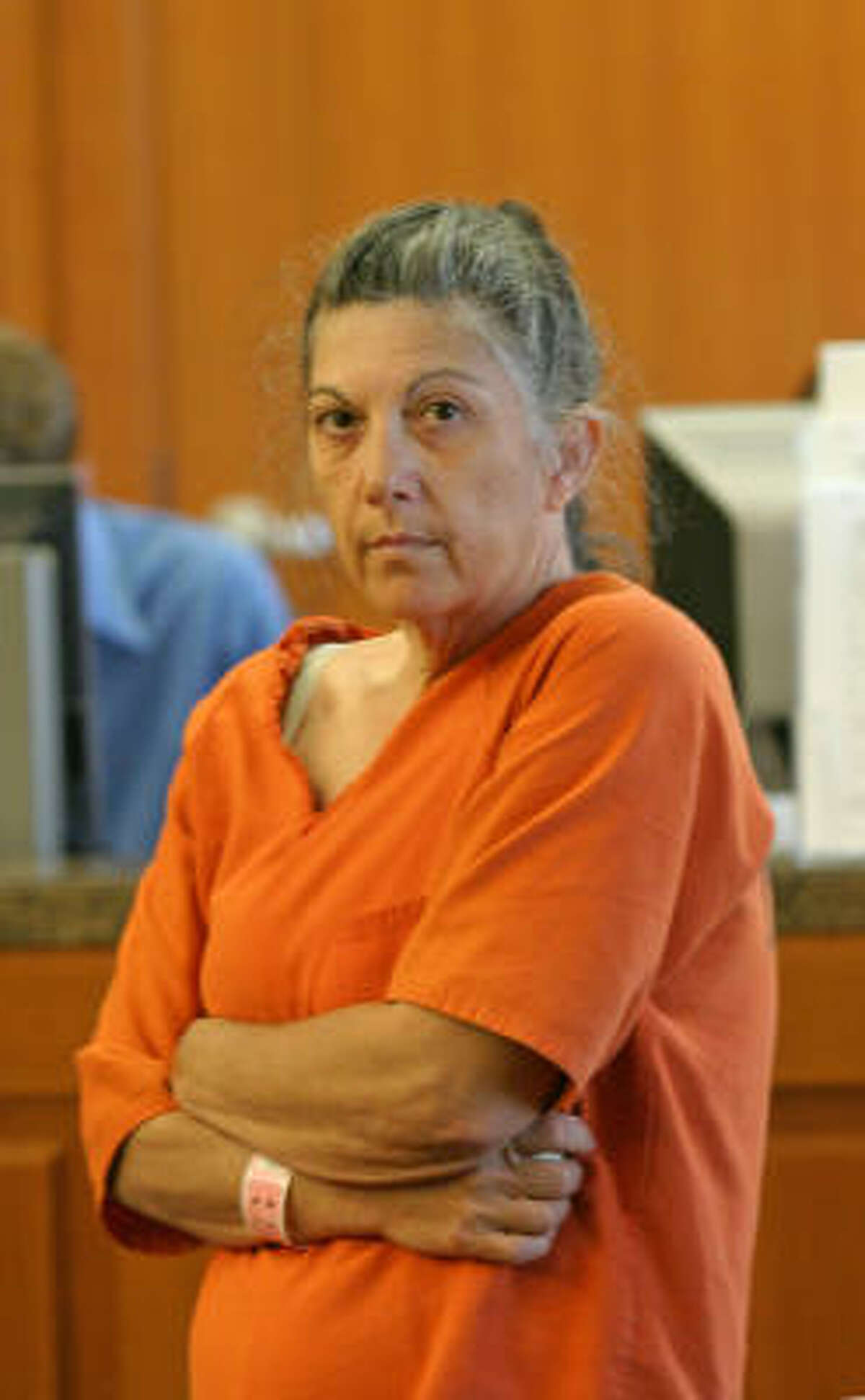 Linda A. Ballew waits in civic court to return to the county jail where she was to be released after her hearing in Judge Mark Davidson's 111th District Court. Ballew had been found in contempt of court for not cutting her grass and trimming her trees as the judge had ordered her to do.