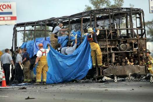 Firefighters work to cover the bodies of nursing home evacuees from Bellaire who died Sept. 23, 2005, when the bus they were fleeing Hurricane Rita in caught fire on Interstate 45, south of Dallas. Photo: JIM MAHONEY, AP