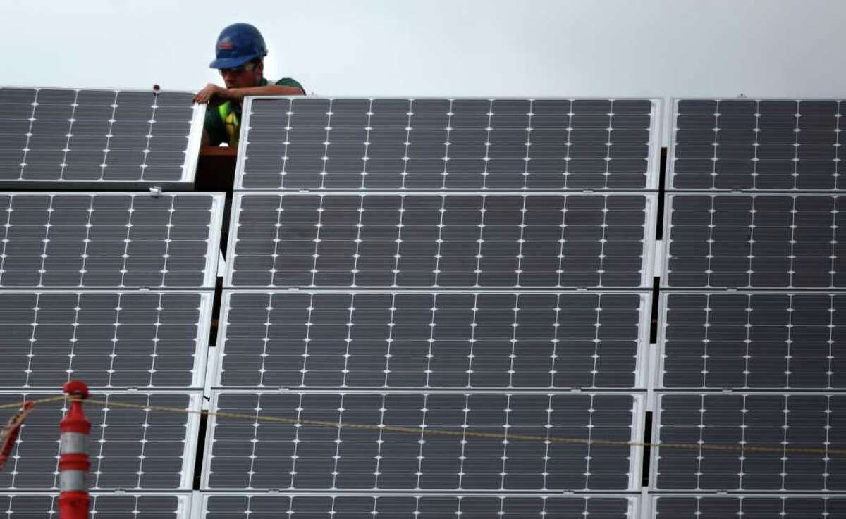 A worker installs solar panels atop Lake City Village affordable housing in Seattle's Lake City neighborhood on May 24, 2011.