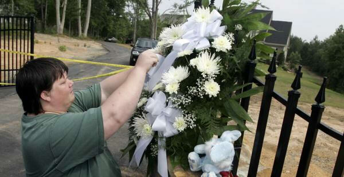Jimmy Baswell leaves flowers and a note outside Benoit's Fayetteville, Ga., home Tuesday.