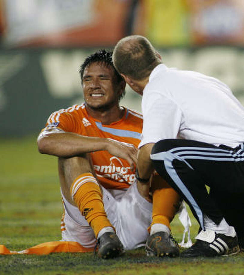 Brian Ching is treated on the field at Saturday's game against Kansas City. Photo: Nathan Lindstrom, For The Chronicle