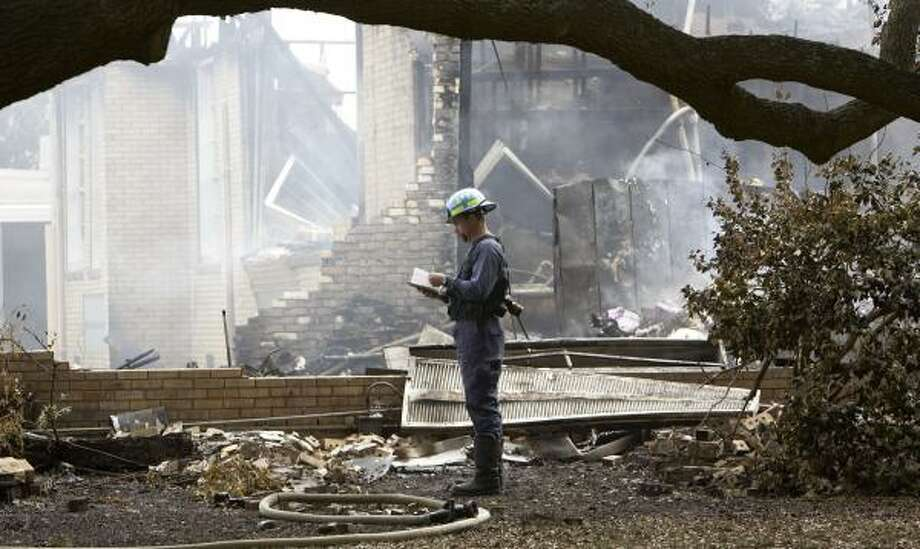 An investigator inspects the area of Needville High School damaged by fire early Monday. Needville is about 40 miles south of Houston. Photo: BOB LEVEY, FOR THE CHRONICLE