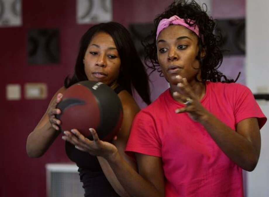 Personal trainer Bethany Dockett, left, passes the ball to Sonia Davis as part of a flexibility exercise during her workout. African-American women are reluctant to work out, citing cultural expectations, causing some experts to worry about their health. Photo: KAREN ELSHOUT, ST. LOUIS POST-DISPATCH