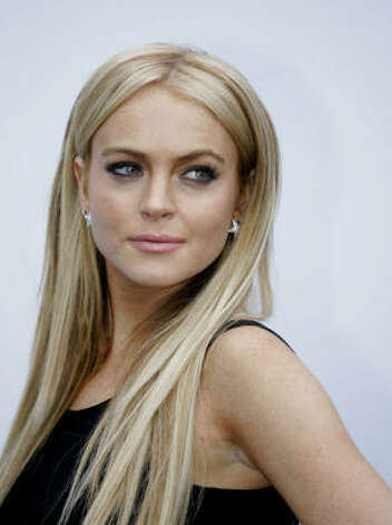 Lindsay Lohan is shown in this May 18 file photo in Santa Monica, Calif. Lohan was cited for investigation of driving under the influence Saturday and was slightly injured when her Mercedes convertible struck a curb, police said. Lohan, 20, and two other people were in her 2005 Mercedes SL-65 when it crashed on Sunset Boulevard around 5:30 a.m., Sgt. Mike Foxen said. Photo: Mark J. Terrill, ASSOCIATED PRESS