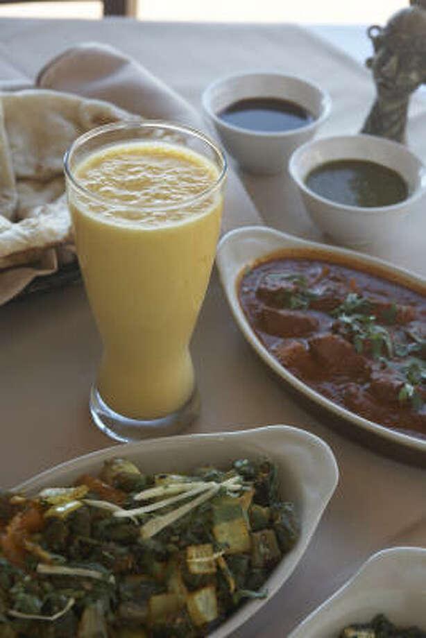 Naan and a glass of mango lassi accompany lamb vindaloo and bindhi do piaza, from the menu at Moksha Indian Fusion Cuisine. Photo: Gabriella Nissen, For The Chronicle