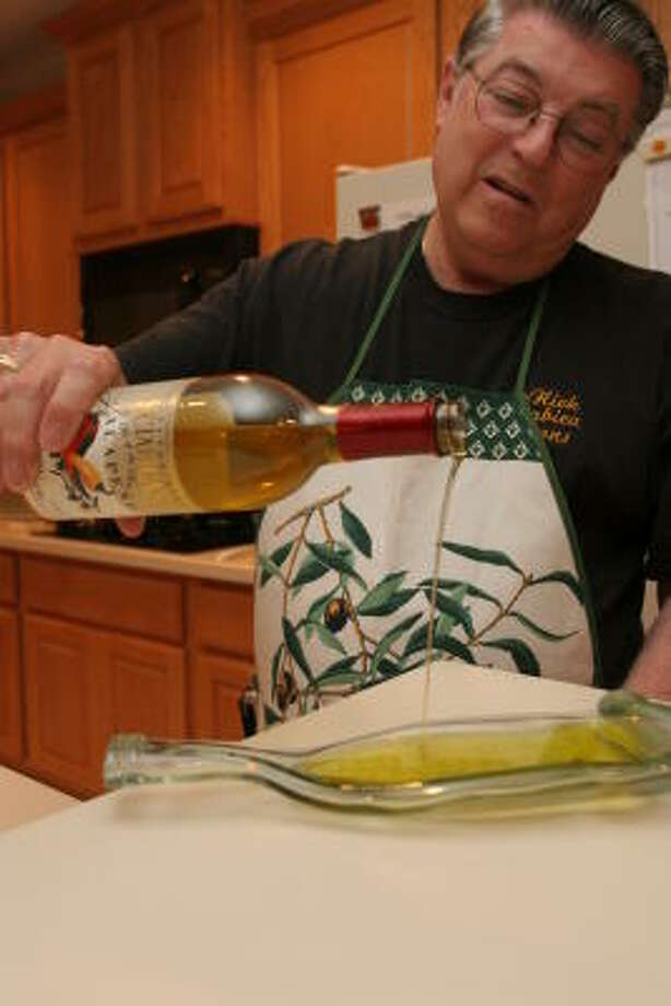 David Laufenberg pours some of his jalepeno infused olive oil on a wine bottle shaped plate for dipping with bread. Photo: Kenzie DelaTorre, For The Chronicle