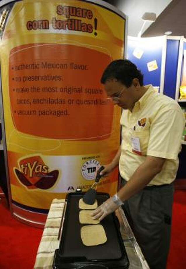 Edgar Anaya, brother of the president of Anacom Alimentos, heats up some tiYas — square corn tortillas — at Expo Comida Latina on Monday at the George R. Brown Convention Center. Nearly 190 food makers participated in the event. Photo: KAREN WARREN, CHRONICLE