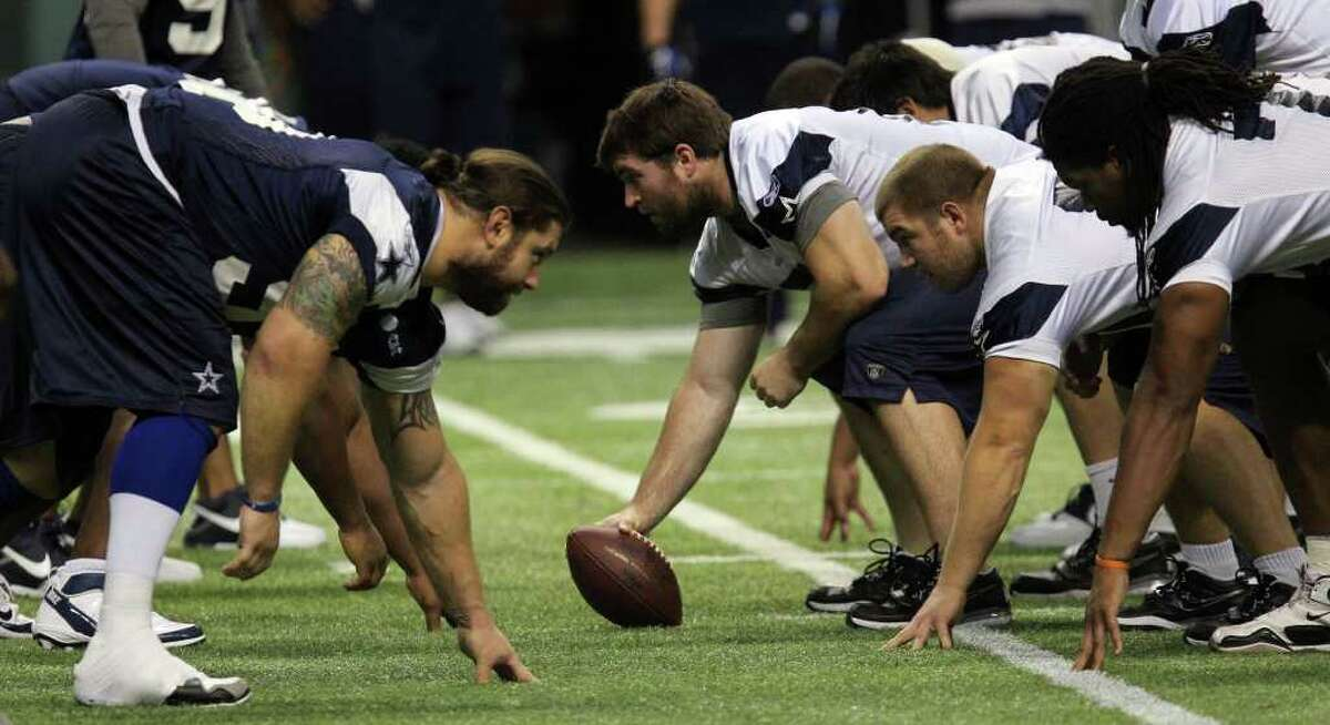 Cowboys defense (blue, left) and offense (white, right) head off during training camp at the Alamodome on Tuesday, Aug. 9, 2011.