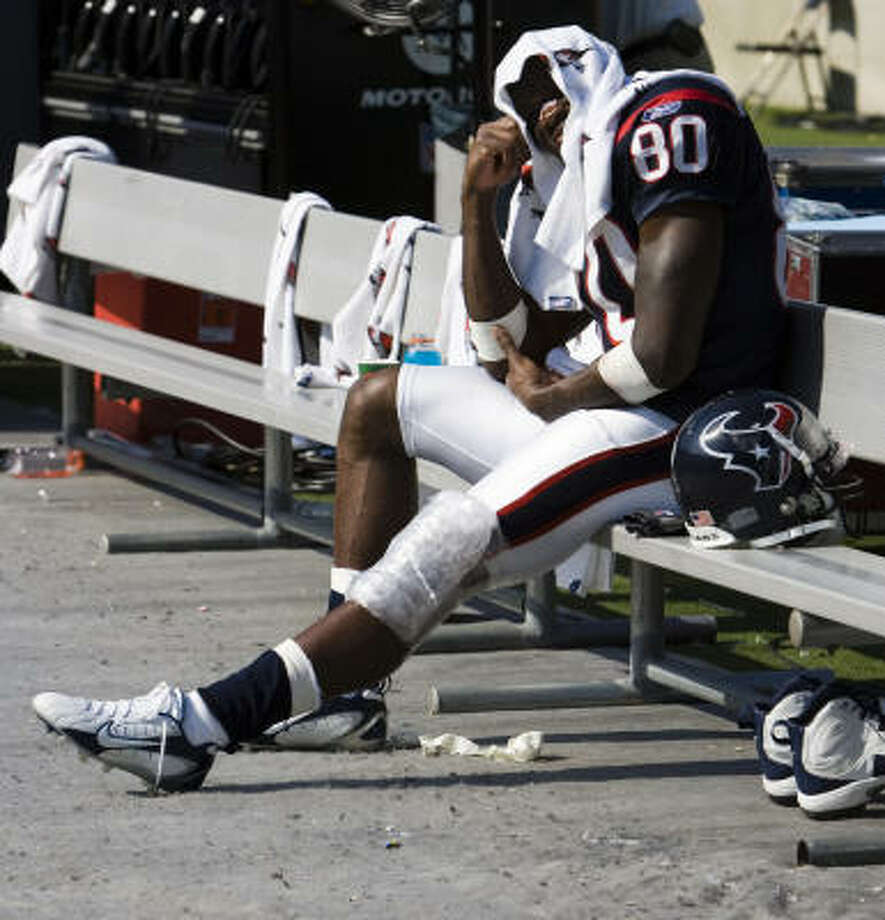 Andre Johnson sits on sidelines with ice on his left knee during the Texans 34-21 victory on Sunday. Photo: Smiley N. Pool, Chronicle