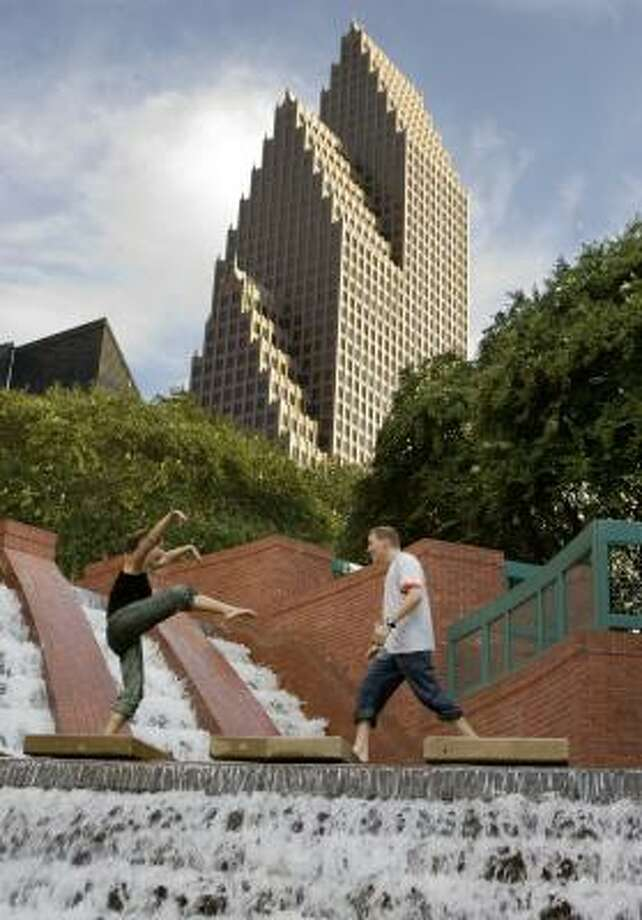 With the Bank of America Center behind them, Amanda Manzer and Joseph Chapman have fun downtown on Thursday. The building was designed by Philip Johnson and John Burgee. Photo: BRETT COOMER, CHRONICLE