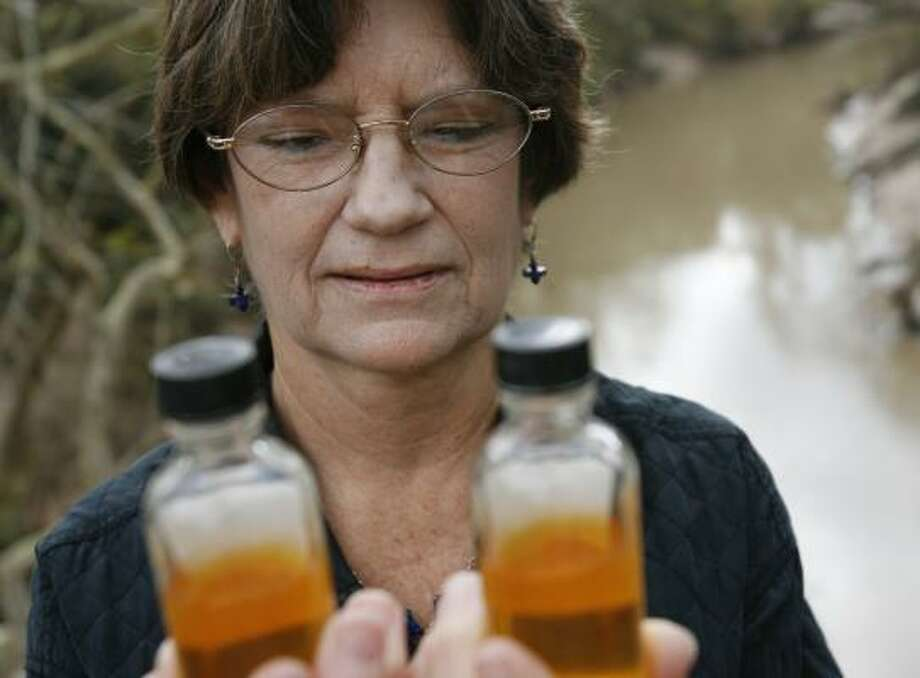 Mary Ellen Whitworth, executive director of the Bayou Preservation Association, collects liquid from Buffalo Bayou every month to test for oxygen and bacteria levels. Photo: SHARÓN STEINMANN, CHRONICLE