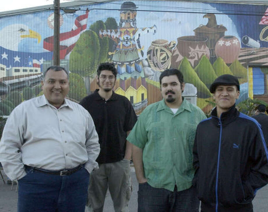 Philip Perez, right, in front of a mural he helped paint with Jesse Sifuentes, from left, Ulysses Penfield and Joseph Sifuentes in 2003. Photo: Kim Christensen, For The Chronicle