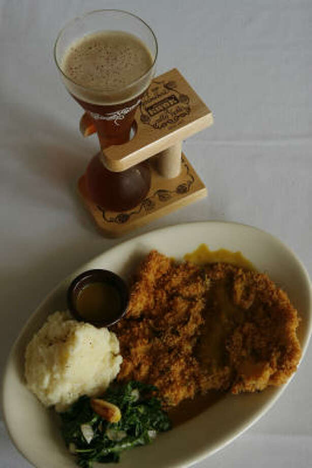 Texas schnitzel with mustard-ale sauce is a sophisticated take on chicken-fried steak at J's Bistro. Here it is served with Pauwel Kwak beer from Belgium. Photo: Steve Campbell, Chronicle