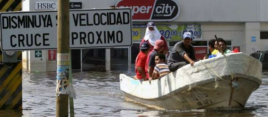 Residents are driven in fishing boats along flooded streets in Villahermosa on Tuesday. Oil fields in the Mexican region are largely unscathed, but many oil workers have lost their homes. Photo: GILBERTO VILLASANA, AFP/GETTY IMAGES