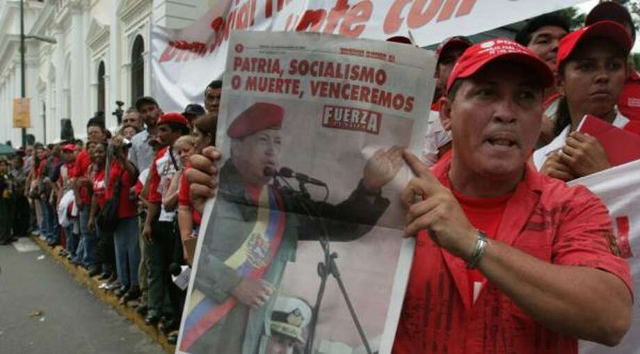A supporter of Venezuela's President Hugo Chavez displays a poster with a picture of Chavez in Caracas on Wednesday. Photo: HOWARD YANES, ASSOCIATED PRESS