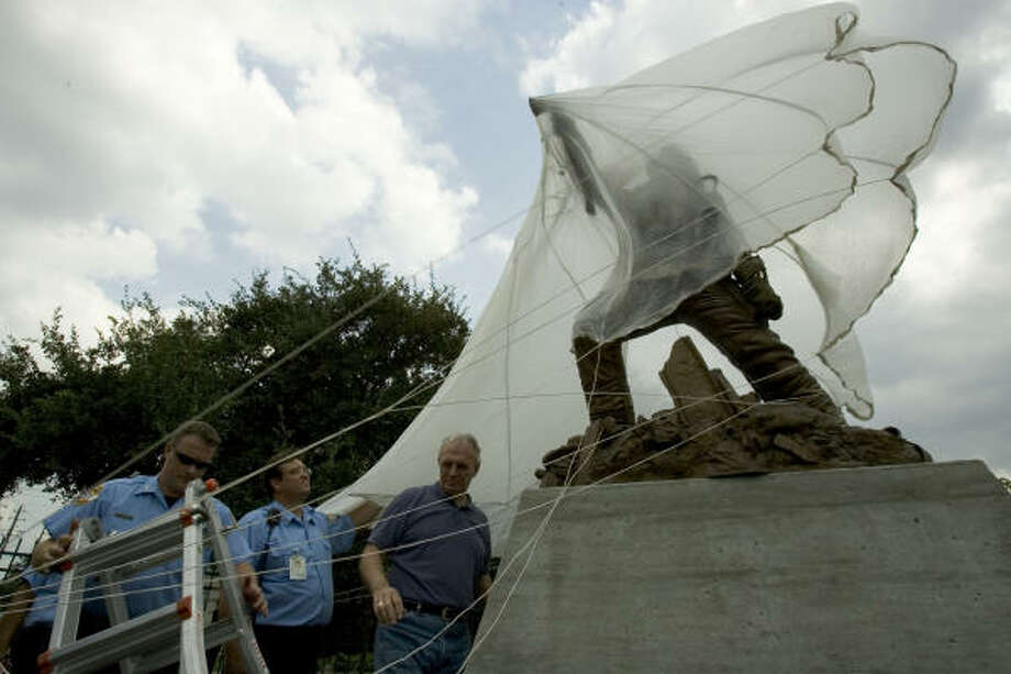 "Houston firefighters, Shannon Stryk, left, and Harold Ryan, of Houston FD Ladder 7, help artist Edd Hayes cover ""In the Line of Fire"" with a parachute at the site of a future educational unit of the Houston Fire Museum. The sculpture will be unveiled today. Photo: Brett Coomer, Chronicle"