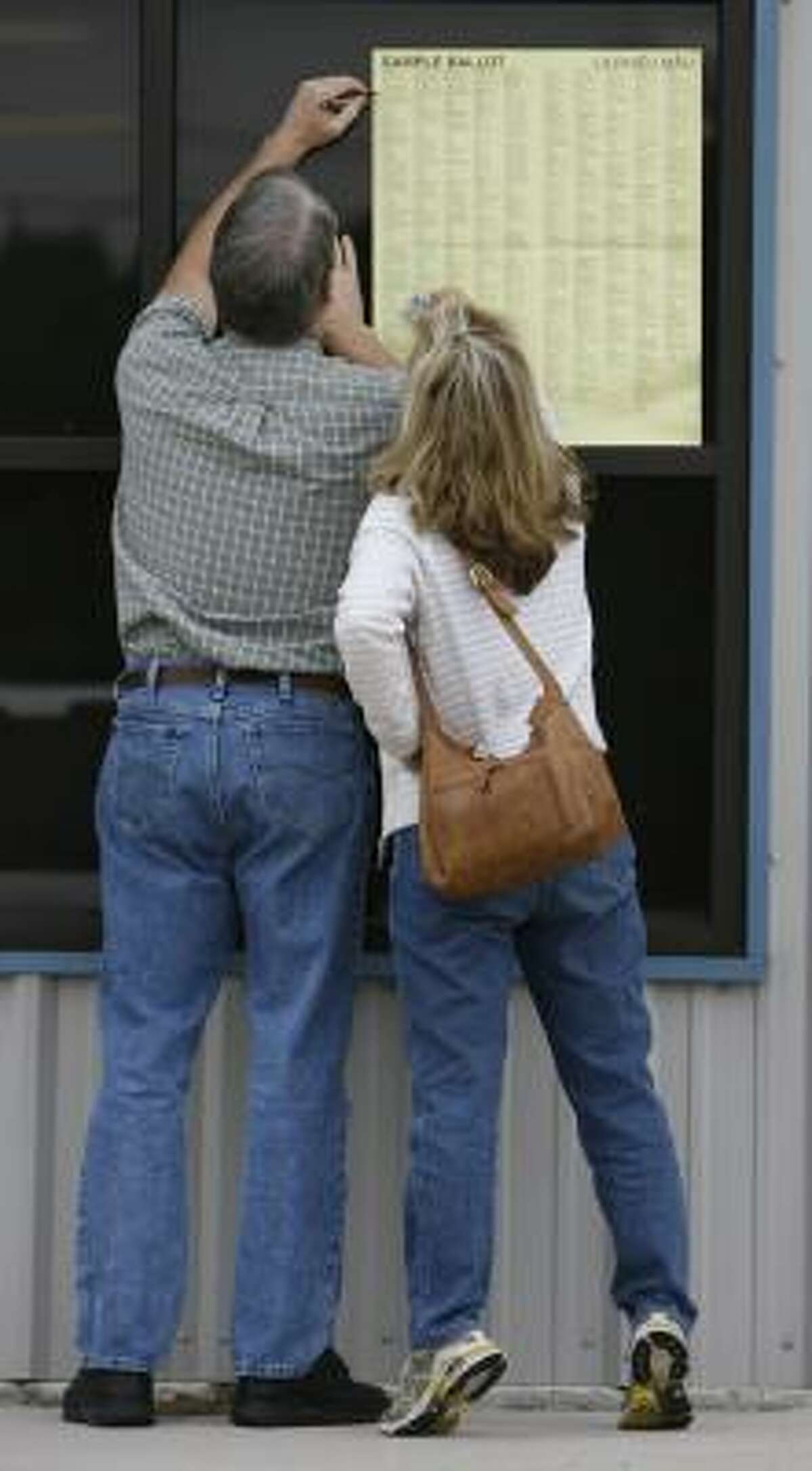 Before voting, Ed and Ellen Moers of Cypress read a sample ballot Tuesday outside the Precinct 126 polling place at Rosehill Volunteer Fire Department in Tomball. Most precincts in the area reported low voter turnout for this election.