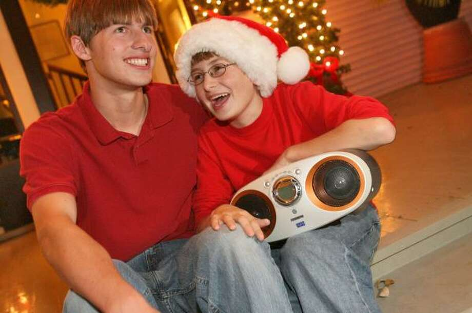 Matthew Robbins, left, and brother Sam listen to music while checking out neighborhood Christmas lights. Photo: Bill Olive, For The Chronicle