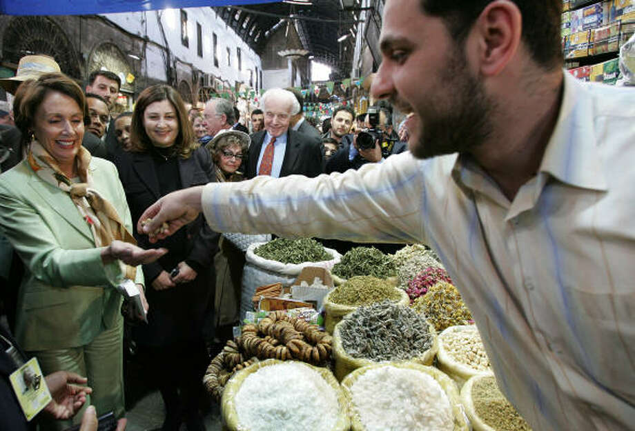 A Syrian vendor offers nuts to House Speaker Nancy Pelosi at a popular market Tuesday in downtown Damascus. President Bush has criticized Pelosi's trip, saying it sends mixed signals. Photo: HUSSEIN MALLA, AP