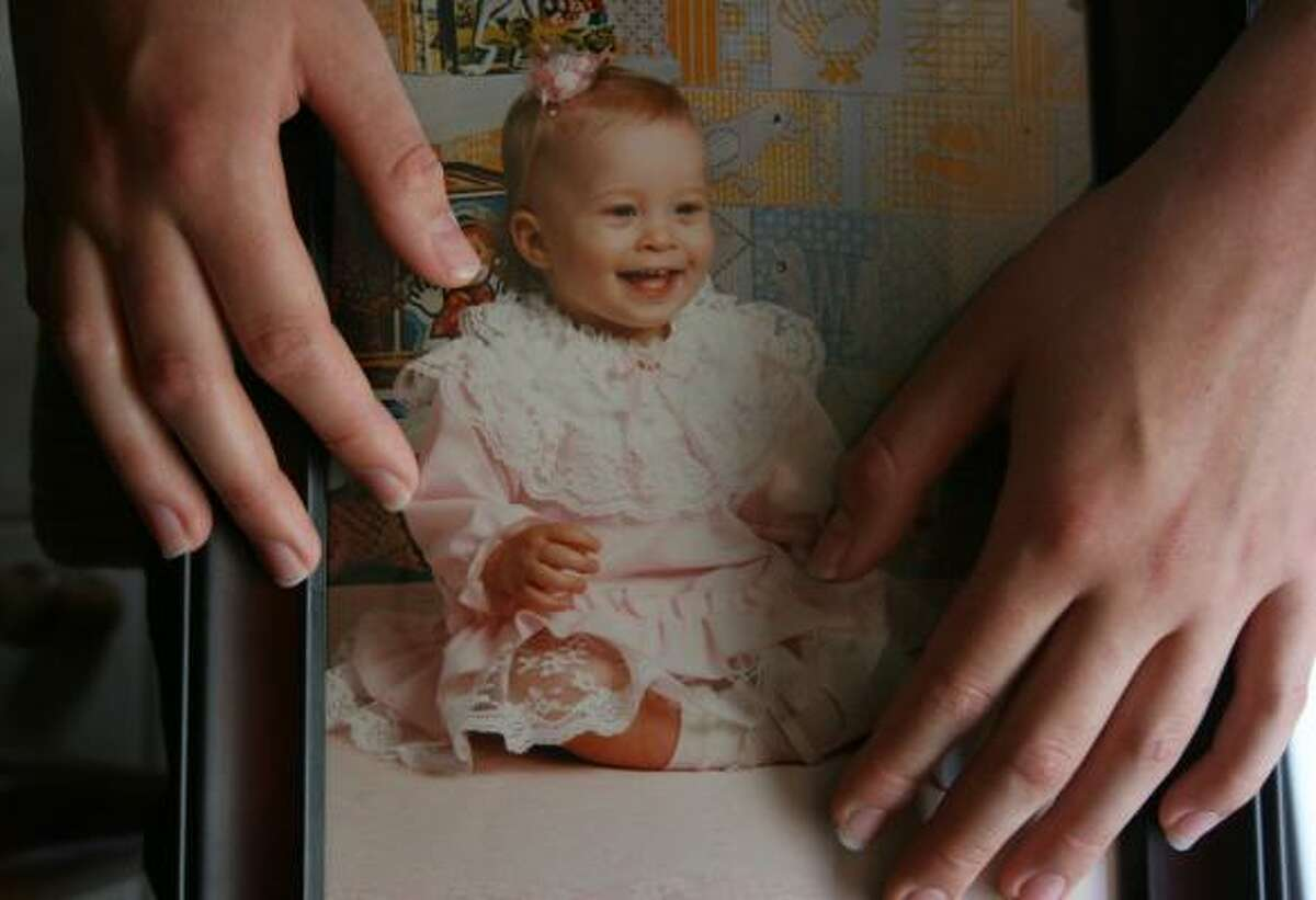 Jessica, 21, holding a photo of herself as an infant, was born with what used to be called hermaphroditism.