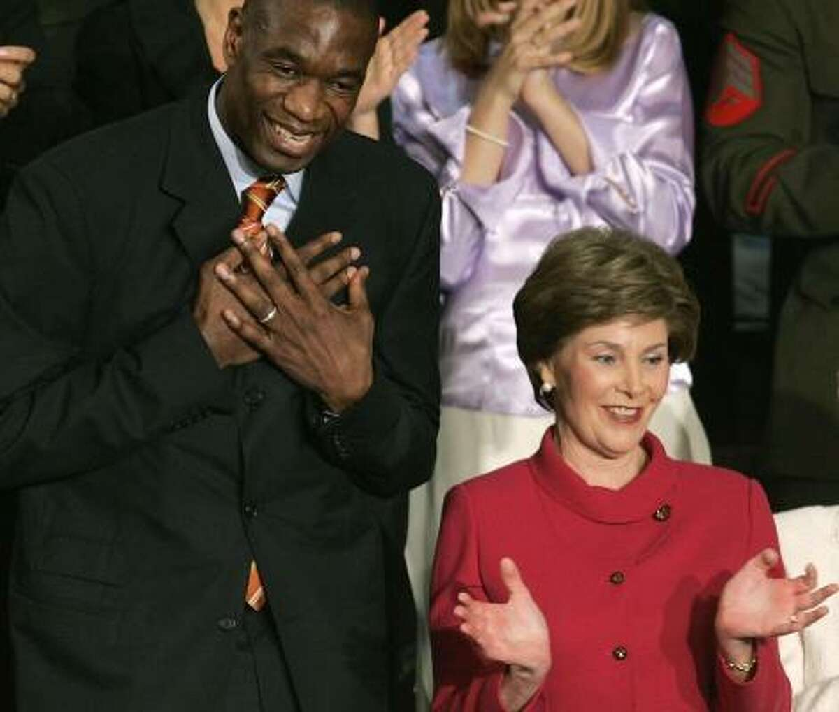 Dikembe Mutombo, left, acknowledges applause at the U.S. Capitol. Mutombo was honored during Bush's speech as an example of