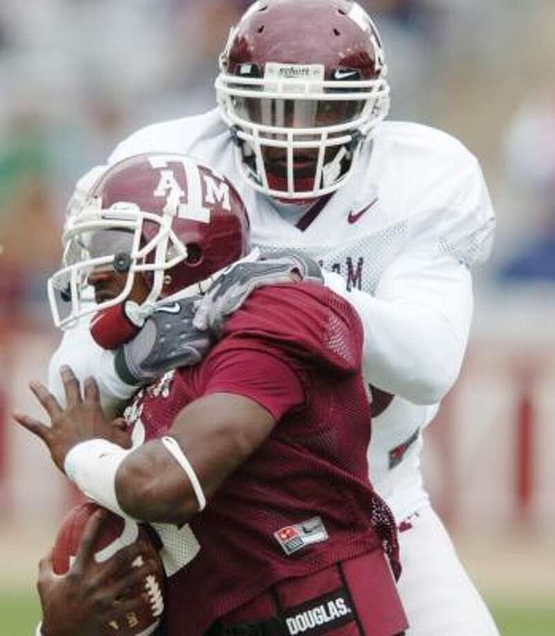 Cyril Obiozor brings down QB Jerrod Johnson, a product of Humble, at the Maroon and White game. Photo: Dave McDermand, AP
