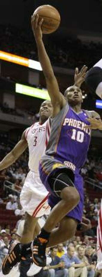 Steve Francis, left, takes a swipe at a shot by the Suns' Leandro Barbosa on Saturday night. Photo: DAVID J. PHILLIP, AP