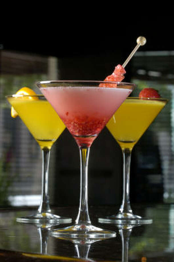 Sip someething a little different, such as an Electric Raspberry martini, foreground, or His and Hers Mango martinis at the Sam Bar in the Sam Houston Hotel. Photo: BRETT COOMER, HOUSTON CHRONICLE