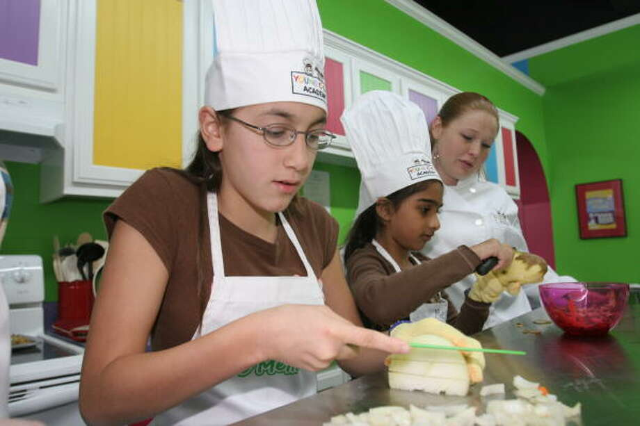 Kaylene Mesecher, 12, cuts onions, while Meghna Arya, 8, peels and cuts potatoes as instructor Lisa Rhodes observes as Young Chefs Academy. Photo: Suzanne Rehak, For The Chronicle