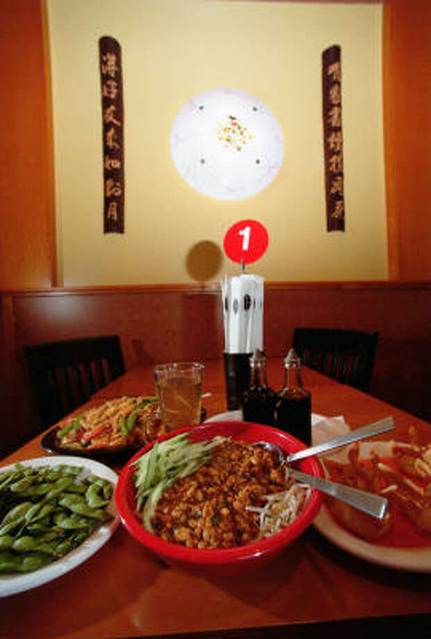 Dan-Dan Noodle Bowl, center, offers minced chicken in a brown sauce. It shares space with edamame, left, crab won tons, right, and Blazing Noodles with Shrimp, behind. Photo: Chronicle File