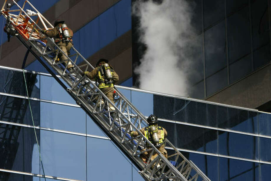 Houston firefighters battle a blaze today at the T. Boone Pickens Academic Tower, a part of the University of Texas M.D. Anderson Cancer Center at the Texas Medical Center in Houston. No one was injured. Photo: Nick De La Torre, Chronicle