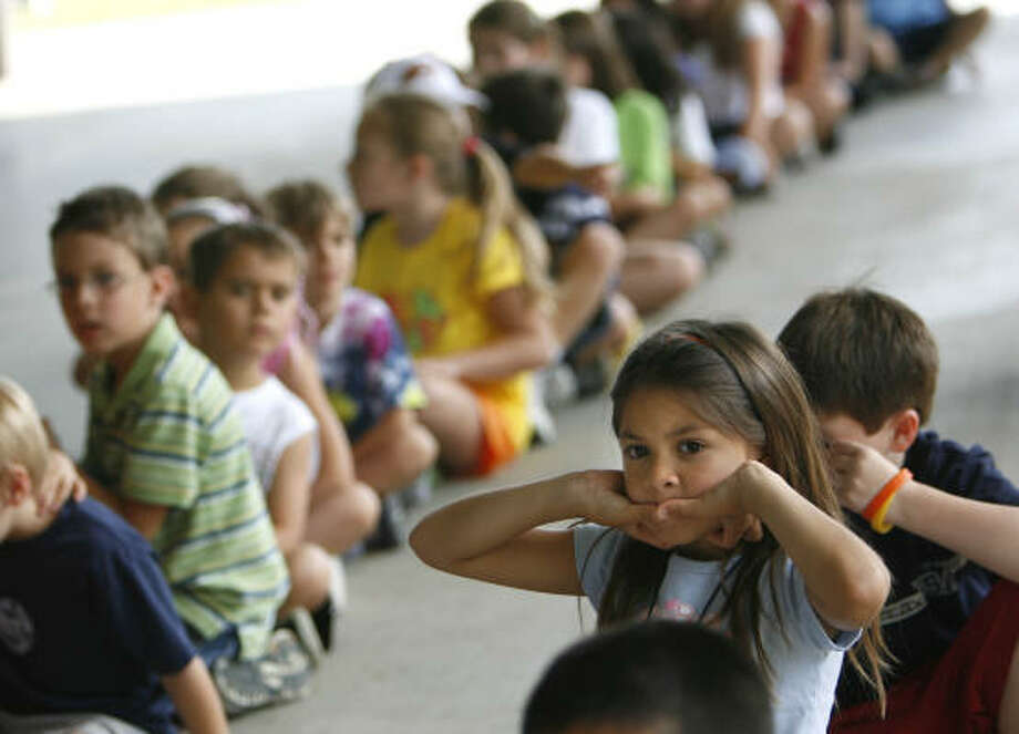 Isabella Ojeda, right, 6, participates in an activity on the first day of summer camp, Tuesday, at Cypress Creek YMCA in Houston. Photo: SHARÓN STEINMANN, Chronicle