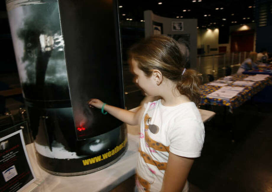 Chasity Herman, 11, of Baytown, sticks her hand into the Tornado Chamber in the Kids Zone, which was provided by The Weather Museum, at the Houston/Galveston National Weather Service's 2007 Hurricane Workshop at the George R. Brown, Saturday. Photo: Karen Warren, Chronicle