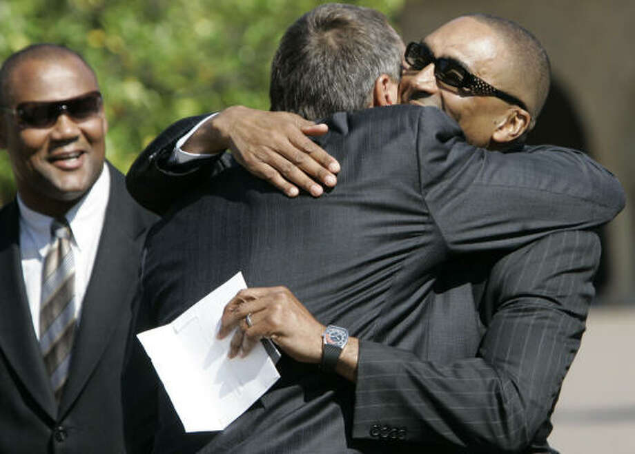 Former San Francisco teammates Dwight Clark and Roger Craig embrace during Bill Walsh's memorial service. Photo: Jeff Chiu, AP