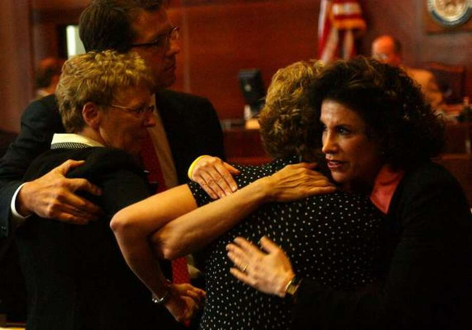 Carol Ernst, left, attorney Mark Lanier, Ernst's daughter Shawna Sherrill and attorney Lisa Blue hug after Sherrill's testimony in the 2005 Vioxx trial. Photo: CARLOS ANTONIO RIOS, CHRONICLE FILE