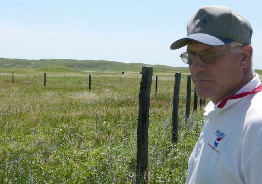 Rancher Duane Kime stands at the fence that separates his land from Ted Turner's in Mullen, Neb. Kime is concerned about what the CNN founder plans to do with his land. Photo: NATE JENKINS, ASSOCIATED PRESS