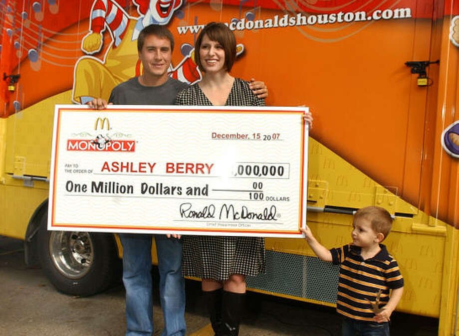 Ashley Berry, 25, center. of Kingwood, with her husband, Jay, left, and their son, Blake, 2, is all smiles after being presented her ceremonial check for $1 million for winning the McDonald's Monopoly prize at the McDonalds store on North Park Drive in Kingwood on Saturday. Photo: Jerry Baker, For The Chronicle