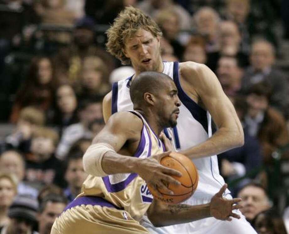 Sacramento's Corliss Williamson, left, operates under the looming presence of Dirk Nowitzki, who led the Mavs with 32 points. Photo: TONY GUTIERREZ, ASSOCIATED PRESS