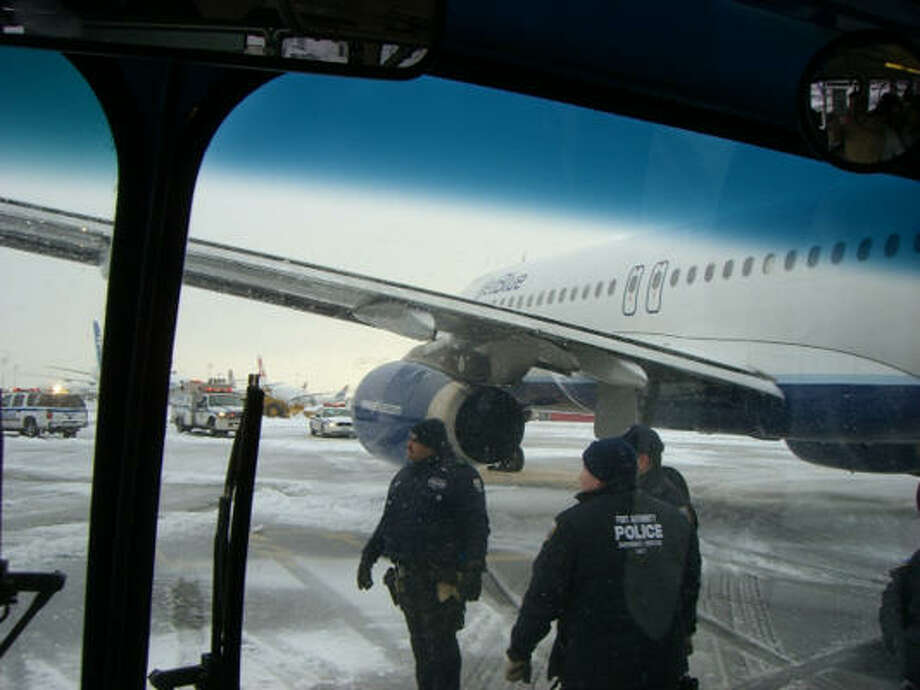 A cell-phone photo taken by a passenger shows police helping fliers leave a stranded jet. Photo: LOU MARTINS, AP
