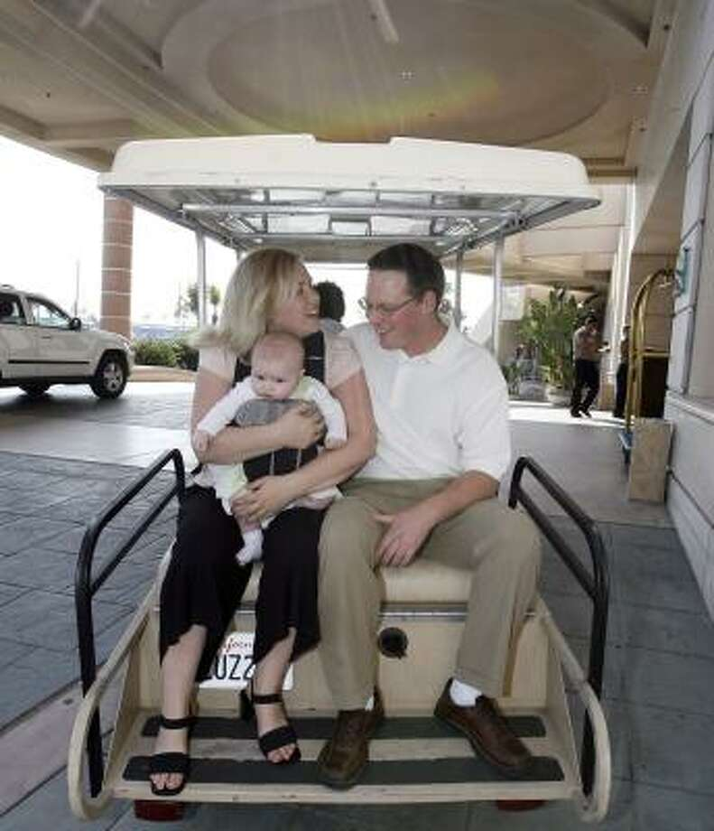 """Deanna and Kurt Barrett and 5-month-old daughter Ava ride in a golf cart in Coronado, Calif. More flexibility from employers means that more travelers can take family along on business trips. """"Work is very important, but there has to be a balance,"""" Kurt Barrett says. Photo: DENIS POROY, ASSOCIATED PRESS"""