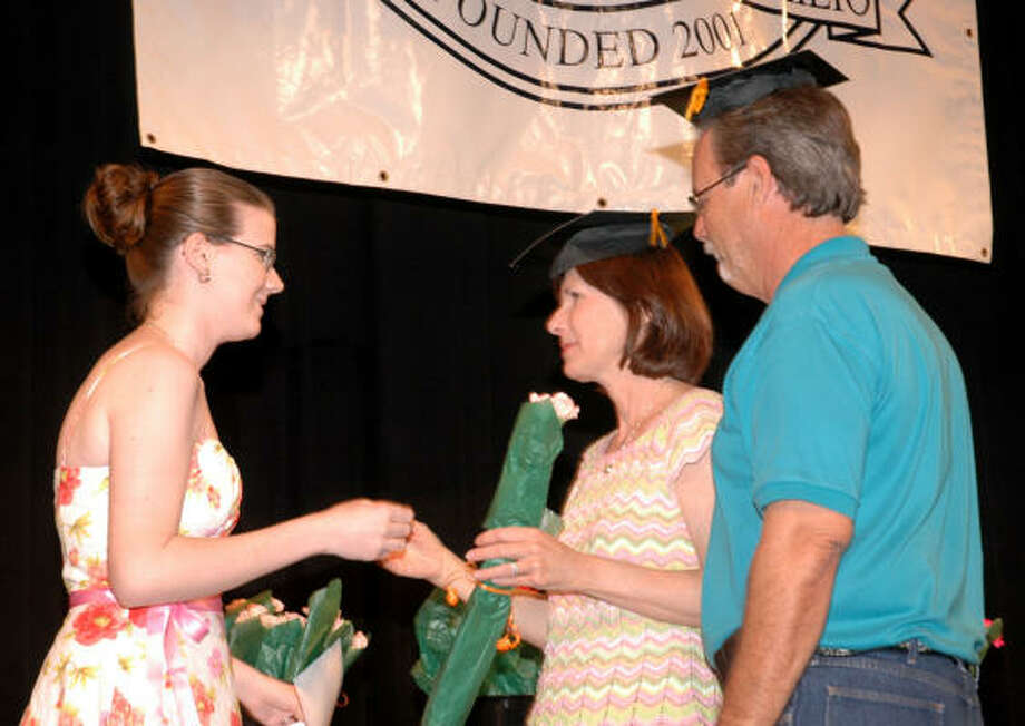 Susan and James Stillwagon receive a cap and a diploma from their daughter Kaila, left, during parent appreciation night. Photo: George Wong, For The Chronicle