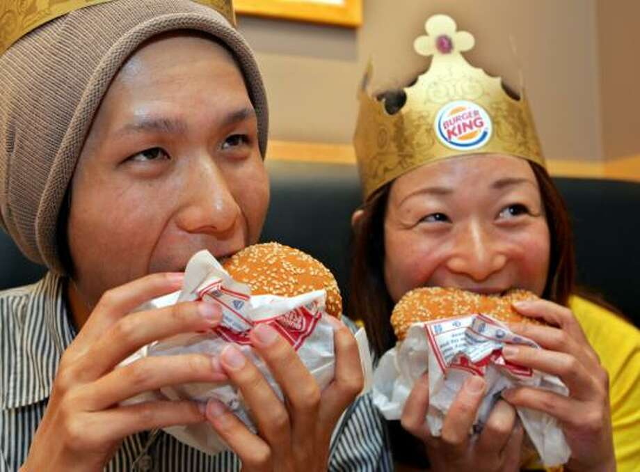 Daiki Hokotate, left, and Momoka Tanaka, right, the first customer at Tokyo's new Burger King, bite into Whoppers on Friday. Photo: KOJI SASAHARA, ASSOCIATED PRESS