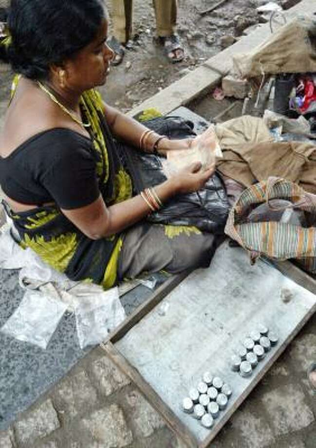 A woman, selling stacks of 100 rupee coins for 120 rupees, counts notes at a bus stand in Calcutta, India. Photo: BIKAS DAS, ASSOCIATED PRESS