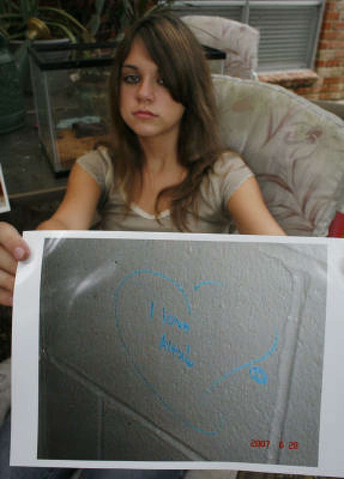 """Shelby Sendelbach displays a photo Thursday of the grafitti, """"I love Alex"""" that the sixth-grader wrote on a gym wall."""