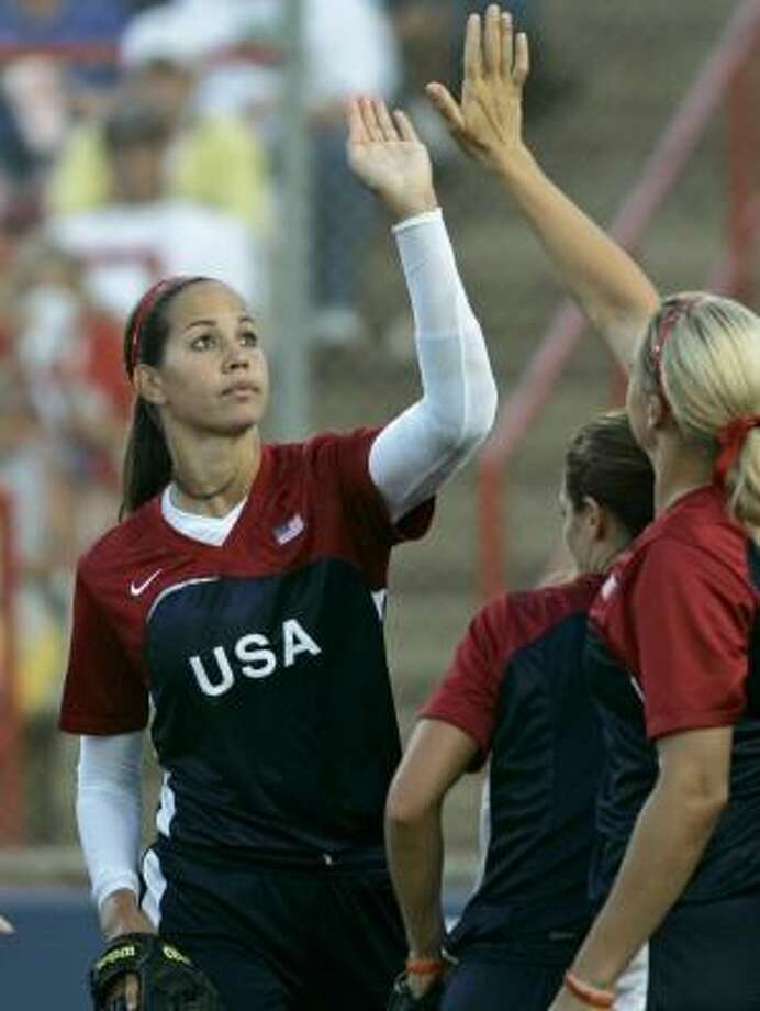Cypress Springs product Cat Osterman, left, is the recipient of high-fives after blanking China. Photo: ASSOCIATED PRESS