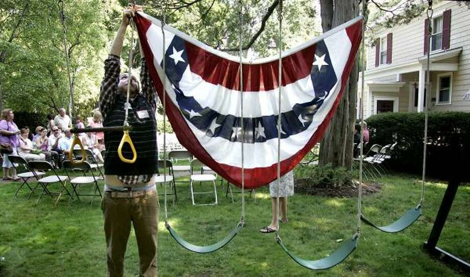 Jeff Thibodeau, with John Edwards' campaign, affixes a flag to a swing set for a house party in Nashua, N.H., on Saturday, where Edwards was scheduled to speak. Photo: CHERYL SENTER, ASSOCIATED PRESS