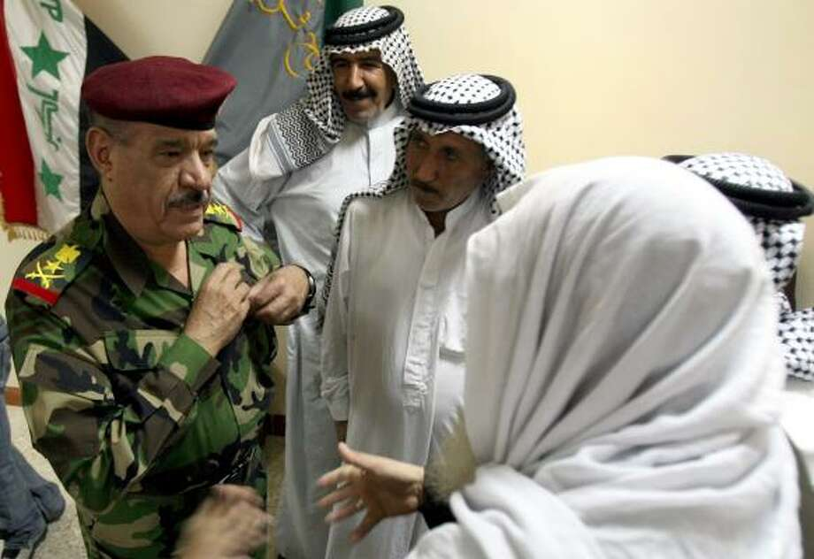 Lt. Gen. Abboud Qanbar, left, discusses Monday's rescue operation with sheiks Abdel-Majeed Rasheed Naseef, left, Mudhur al-Azawi and Haroon al-Mohammedawi, back to camera. Photo: HADI MIZBAN, ASSOCIATED PRESS