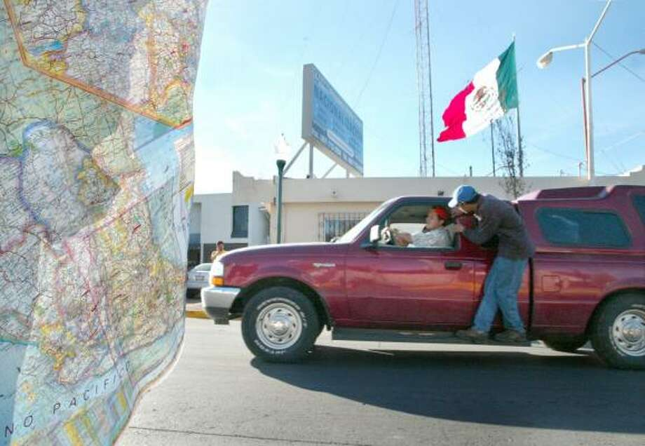 A worker for a naturalization service encourages a man to use his company as he crosses the Juarez-Lincoln International Bridge last week into Mexico. Most returning home are legal U.S. residents. Photo: RICARDO SEGOVIA, LAREDO MORNING TIMES