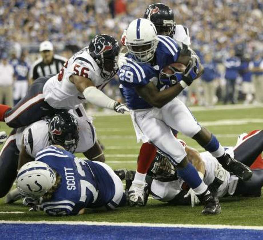 At left, Indianapolis' Joseph Addai heads untouched into the end zone in the second quarter; at right, Reggie Wayne hauls in a 42-yard pass in front of Von Hutchins. Photo: Brett Coomer, Chronicle