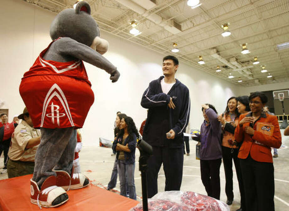Rockets center Yao Ming, center, hams it up with Rockets mascot Clutch during a visit to the Chinese Community Center in recognition of the Lunar New Year on Monday. Yao's been out with a broken leg but is getting closer to returning to action for the Rockets. Photo: KAREN WARREN, Chronicle